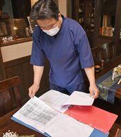 4、5月の予約帳を見つめる大和屋の山口勝也専務。大型連休中は県内からの宿泊客で埋まっているが、平日は例年の約50%という=佐賀市富士町