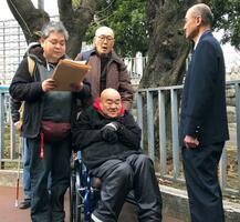 内閣府の担当者(右端)に質問状を読み上げる障害者団体のメンバーら=7日午前、東京都千代田区