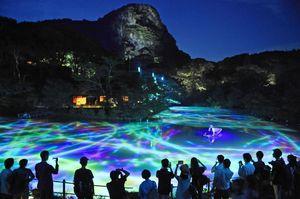 御船山をバックに幻想的な世界を描いた水面ドローイング=武雄市の御船山楽園、7月13日撮影