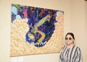 竹下綾香さんと作品「境界午睡」(1167センチ×910センチ、アクリル絵の具など)=佐賀市のトネリコカフェ