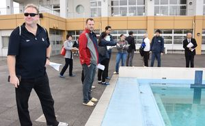 屋外プールを見学するカナダ水泳連盟の視察団=佐賀市の県総合運動場水泳場