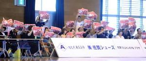ハーフタイムには赤い表紙の特集紙面を掲げて一斉に応援した=神埼市の神埼中央公園体育館