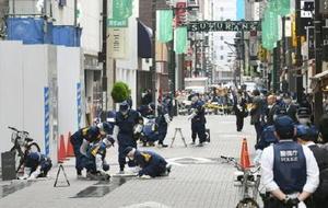 現金数千万円入りのバッグを奪われたとの通報を受け、現場付近を調べる警視庁の捜査員=21日午後3時1分、東京都中央区銀座