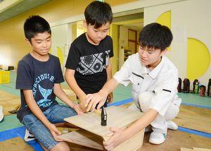 唐津工高の生徒と一緒にくぎ打ちに挑戦する児童=唐津市の佐志小