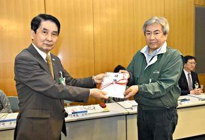 東島正明教育長(左)に目録を手渡す池田龍二さん=佐賀市の市立図書館