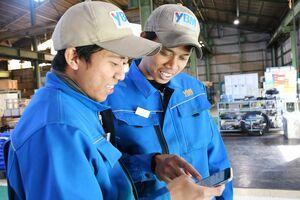 インドネシア語で届いた緊急速報メールを見る外国人技能実習生=唐津市北波多のワイビーエム岸山工場