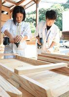 機械を使ってねじを取り付ける高校生たち=佐賀市富士町の黒田木材商事工場