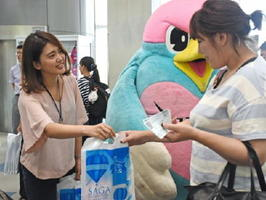 帰省客にPRグッズを配る佐賀市の職員とサガン鳥栖マスコットキャラクターのウィントス=佐賀空港