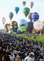 熱気球世界選手権の公式練習で、大空へ一斉に飛び立つバルーン=30日、佐賀市の嘉瀬川河川敷