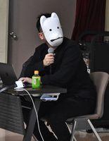 白いお面をつけて自身の経歴などを語るwatabokuさん=佐賀市本庄町の佐賀大学