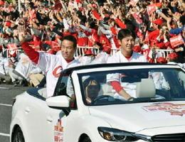 プロ野球広島カープのセ・リーグ優勝を祝うパレードで、沿道のファンに手を振る黒田博樹投手(左)と新井貴浩選手=5日午前、広島市