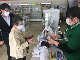 スマホ決済を実践して、買い物をする教室の参加者(左から2人目)=鹿島市内のコンビニ店