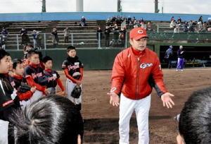 子どもたちにグラブの芯でボールを捕るよう、熱く指導するプロ野球・広島の緒方孝市監督=鳥栖市民球場