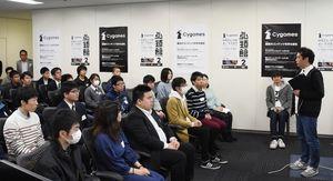 参加者を前に、デバッグ業務の説明や佐賀の印象を語る平岡徹也センター長(右)=佐賀市のiスクエアビル