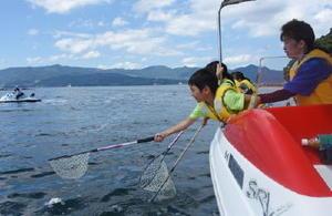 網を精一杯伸ばして漂流するごみなどを拾う子どもたち=伊万里湾内