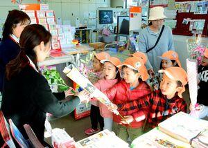 郵便局員に感謝の気持ちを伝えながら、花を手渡すちとせ保育園の園児たち=神埼市千代田町の千歳郵便局