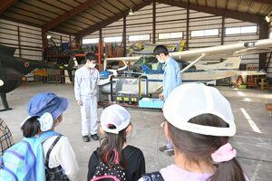 子どもたちに飛行機が飛ぶ仕組みを教える北陵高の生徒たち=佐賀市の同校
