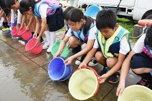 バケツに入ったエツの稚魚を筑後川に放流する三根西小の児童たち=久留米市の下田大橋付近