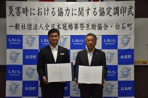 協定を結んだ全日本冠婚葬祭互助協会の吉田昌敬理事(左)と田島健一町長=白石町役場
