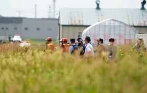 クマが出たとの通報があり、警戒する北海道警の警察官ら=18日午前9時39分、札幌市