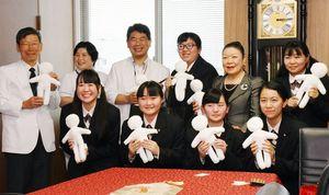佐賀キワニスクラブの大嶋会長(後列右から2人目)と人形を製作した牛津高の生徒ら=佐賀市の県医療センター好生館