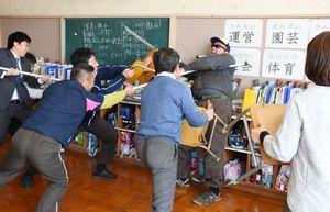 刺股やいすをつかって不審者を取り押さえる訓練に取り組む教諭ら=みやき町の中原小