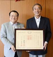 伝達式で謝辞を述べた樋口久俊市長と、紺綬褒章を受けたエスティ工業の里民則社長(右)=鹿島市役所