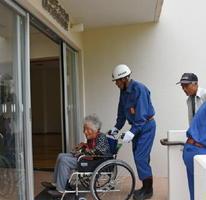 車いすを使って高齢者の放射線防護対策施設への屋内退避をサポートする消防団員=4日、唐津市高島