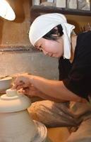 削りの作業に神経を集中させる白須美紀子さん。「作品の大小にかかわらず、丁寧に仕事をするのが第一」と語る=有田町岳の矢鋪與左衛門窯