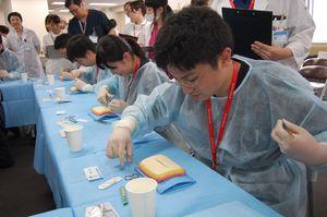 皮膚モデルを使って制限時間内での縫合に挑戦する研修医=福岡県大川市の高木病院