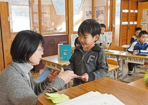 「2学期も頑張ったね」と通知表を渡されうれしそうに受け取る児童=佐賀市立富士小学校