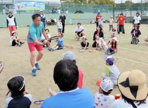 地面にはねさせた球の勢いをラケットで吸収する練習をやって見せる神谷勝則さん=佐賀市の県総合運動場