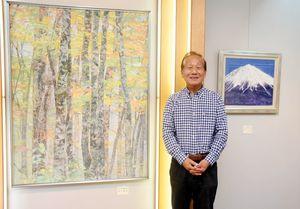 5年ぶりに個展を開いた荒木正次さん。左の作品が県展で知事賞に輝いた「秋の樹林」=佐賀市のぎゃらりぃふじ山