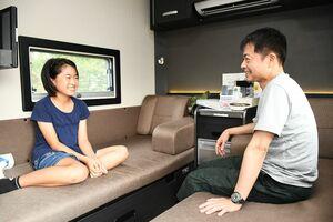 佐賀市が実施するキャンピングカーの宿泊体験に参加し、車内で会話を楽しむ親子=佐賀市東与賀町