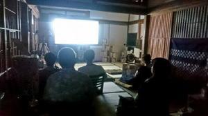 畳敷きの部屋で映画を鑑賞する来場者=佐賀市富士町の泊まれる図書館「暁」