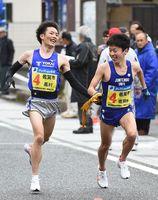 トップに立った佐賀市の嘉村大悟(左)が吉岡幸輝へたすきをつなぐ=14-15区中継所