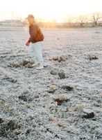 今季一番の冷え込みで霜が降った田畑。作業中の男性が吐く息も白く染まる=21日午前7時ごろ、小城市三日月町
