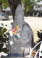 母親を思わせる柔和な表情でタイの代わりに子どもを抱える「子育て恵比須像」=佐賀市白山の龍造寺八幡宮