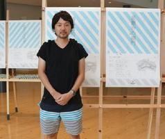 小城市内の古刹・名所を独自のグラフィックデザインでポスターに仕上げた田中淳さん=小城市の交流施設「ゆめぷらっと小城」