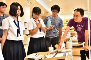 キハラの池田和浩さん(右)から器へ転写する技術の説明を聞く学生ら=有田町のキハラ