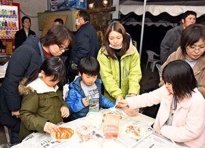 チーズやツナなどの具材を乗せてピザ作りを楽しむ親子=吉野ヶ里町の松本農園