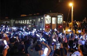大勢の人がペンライトを振って見送る中、JR増毛駅を出発する最終列車=4日夜、北海道増毛町