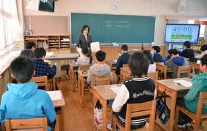6年生のクラスに問題用紙を配る担任教師=佐賀市の赤松小
