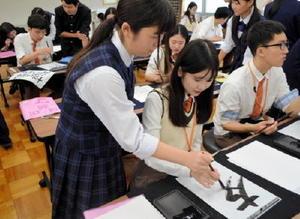韓国の麗水情報科学高の生徒たちに書道を教える唐津商の生徒(提供)