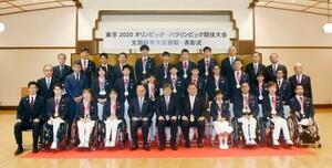 東京五輪・パラリンピックで活躍した選手らの顕彰、表彰式で記念撮影に応じるメダリストら=21日、文科省