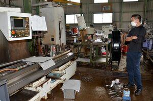 工場が浸水し、復旧作業を続ける弘田傑さん。工作機械が全て水に漬かり、復旧には2カ月ほどかかると見ている=武雄市橘町