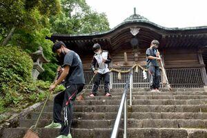 須賀神社の階段をほうきできれいにする小城高陸上部員たち=小城市小城町