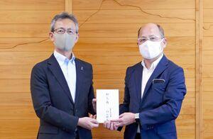 熊本県の村井所長(左)に災害見舞金を手渡した佐賀県の元村所長=東京・平河町の熊本県東京事務所