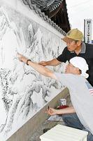 制作している水墨画の表現について話し合う尹さん(手前)と川﨑さん=佐賀市の浄土寺