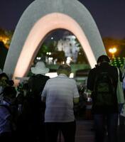 原爆慰霊碑の前で手を合わせる人たち=6日午前4時39分、広島市の平和記念公園